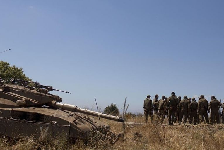 Israeli soldiers are briefed next to a Merkava on the Israeli-Syrian border near Quneitra on June 22