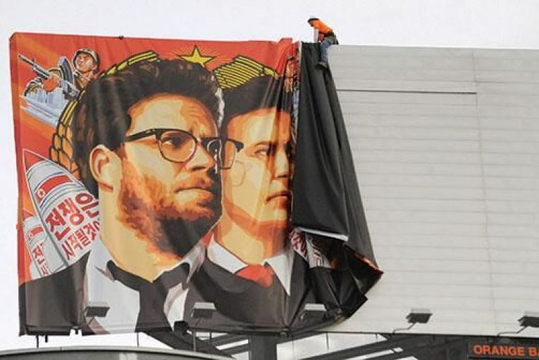 Workers remove a poster  for The Interview from a  billboard in Hollywood last week:  the film eventually got a  limited release over Christmas Picture: Getty