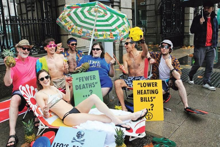 Members of the Extinction Rebellion climate protest group respond to the Taoiseach's comments by bringing their beach wear to the gates of the Dáil Pic: Collins