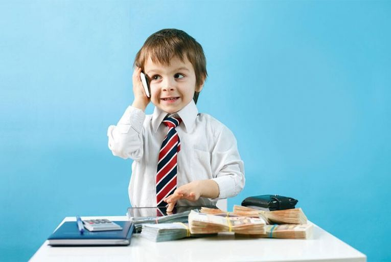 Young boy, talking on the phone, taking notes, money and tablet on the table; Shutterstock ID 581601856