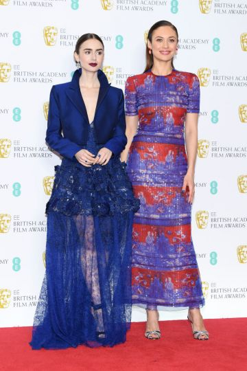 LONDON, ENGLAND - FEBRUARY 10:  Lily Collins (L) and Olga Kurylenko pose in the press room during the EE British Academy Film Awards at Royal Albert Hall on February 10, 2019 in London, England. (Photo by Pascal Le Segretain/Getty Images)