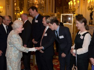 LONDON, ENGLAND - MARCH 25:  Queen Elizabeth II meets Niall Horan (2R) of One Direction at the Irish Community Reception at Buckingham Palace on March, 25, 2014. The reception is in a advance of Ireland's President Michael D Higgins who will be the first Irish President to pay a state visit to Britain in April. (Photo by Steve Parsons - WPA Pool/Getty Images)
