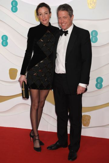 Anna Elisabet Eberstein and Hugh Grant arrive at the EE British Academy Film Awards 2020 at Royal Albert Hall on February 2, 2020 in London, England. (Photo by David M. Benett/Dave Benett/Getty Images)