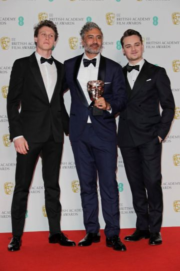 """(L to R)  George MacKay, Taika Waititi, winner of the Best Adapted Screenplay award for """"Jojo Rabbit"""", and Dean-Charles Chapman pose in the Winners Room at the EE British Academy Film Awards 2020 at Royal Albert Hall on February 2, 2020 in London, England. (Photo by David M. Benett/Dave Benett/Getty Images)"""