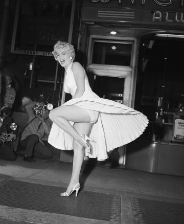 Film star Marilyn Monroe poses over a Manhattan subway grate as the wind blows her white dress up. Photographers capture the moment on camera, which takes place on September 16, 1954, during the filming of Seven Year Itch. Reportedly, Monroe's husband Joe DiMaggio was displeased at the attention his wife received from the crowds.
