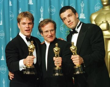 """1998: Actors-writers Matt Damon (L) and Ben Affleck (R) pose with actor Robin Williams with their Oscars they won for """"Good Will Hunting"""" at the 70th Annual Academy Awards 23 March in Los Angeles.  Damon and Affleck won Best Original Screenplay and Williams won for Best Supporting Actor.  (Photo credit should read HAL GARB/AFP via Getty Images)"""