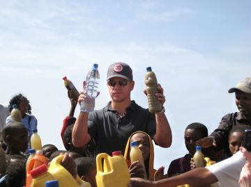 2009: Foundation Ambassador actor Matt Damon visits a well just outside Mekele, Ethiopia on April 20, 2009. In his right hand he holds a bottle of regular water, in his left is a bottle of dirty water local children in Mekele drink everyday.  (Photo by Handout/Getty Images)