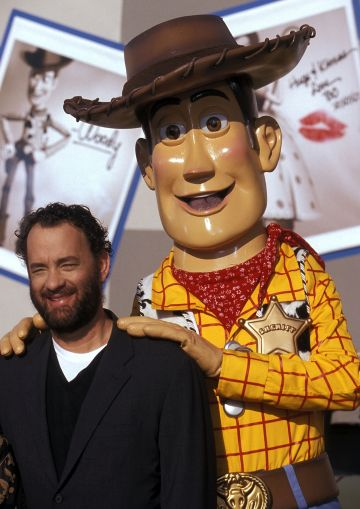 """1999:   Actor Tom Hanks and Woody attend the """"Toy Story 2"""" Themed NASCAR Racing Cars Unveiling on October 23, 1999 at the El Capitan Theatre in Hollywood, California. (Photo by Ron Galella, Ltd./Ron Galella Collection via Getty Images)"""