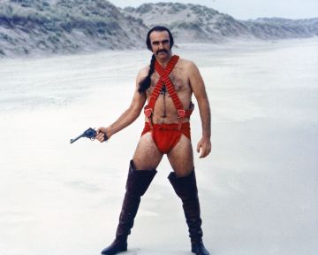 Sean Connery, British actor, holding a handgun while wearing thigh-high boots and red costume, with his hair in a pony tail, standing in a snowy landscape in a publicity portrait issued for the film, 'Zardoz', 1974. The science fiction film, directed by John Boorman, starred Connery as 'Zed'. (Photo by Silver Screen Collection/Getty Images)