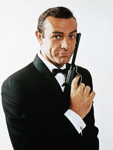 Sean Connery, as James Bond, caressing the barrel of a gun against the side of his face. Connery is wearing a tuxedo and bow tie and smiling slightly. (Photo by Getty Images)