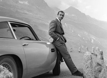 1964:  Actor Sean Connery poses as James Bond next to his Aston Martin DB5 in a scene from the United Artists release 'Goldfinger' in 1964  Photo by Michael Ochs Archives/Getty Images