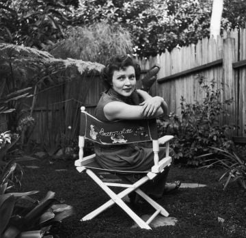 Circa 1956:  American actor Betty White sits in a canvas chair with her name written on the back, looking over her shoulder in a backyard garden.  (Photo by Hulton Archive/Getty Images)