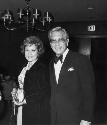 19th March 1974:  American actor Betty White stands smiling with her husband, TV producer and host Allen Ludden (d. 1981), wearing a tuxedo, at an International Broadcasting Awards dinner tribute to Mary Tyler Moore.  (Photo by Frank Edwards/Fotos International/Getty Images)