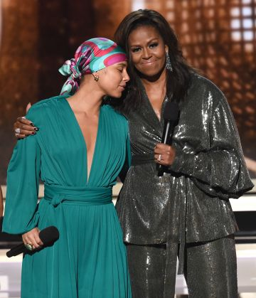 2019:  Alicia Keys (L) and Michelle Obama speak during the 61st Annual GRAMMY Awards at Staples Center on February 10, 2019 in Los Angeles, California.  (Photo by Kevin Winter/Getty Images for The Recording Academy)