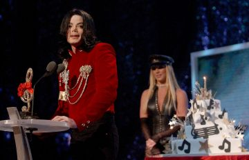 Michael Jackson speaks after Britney Spears presented Michael with a birthday cake at the 2002 MTV Video Music Awards. Britney referred to Michael Jackson as 'the artist of the millennium', causing Michael to accept the non-existent MTV Artist of the Millennium award.  (Photo by KMazur/WireImage)