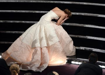 """Actress Jennifer Lawrence trips on her dress while making her way to the stage after winning the Best Actress award for """"Silver Linings Playbook"""" during the Oscars on February 24, 2013 in Hollywood, California.  (Photo by Kevin Winter/Getty Images)"""