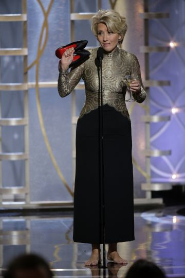 Presenter Emma Thompson arrives onstage during the 71st Annual Golden Globe Awards with her shoes and a martini in hand.  (Photo by Paul Drinkwater/NBCUniversal via Getty Images)