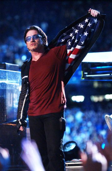 """Bono, lead singer of U2, displays American flag lining in his jacket after singing """"Where The Streets Have No Name"""", during the halftime show of Super Bowl XXXVI in the Superdome, New Orleans, Louisiana, February 3, 2002. (Photo by KMazur/WireImage)"""