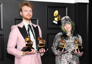 """(L-R) FINNEAS and Billie Eilish, winners of Record of the Year for 'Everything I Wanted' and Best Song Written For Visual Media for """"No Time To Die"""", pose in the media room during the 63rd Annual GRAMMY Awards at Los Angeles Convention Center on March 14, 2021 in Los Angeles, California. (Photo by Kevin Mazur/Getty Images for The Recording Academy )"""