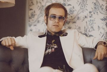 British singer and musician Elton John, wearing a white suit, black shirt with flower motif and multicolored sunglasses, London, November 1973. (Photo by Michael Putland/Getty Images)
