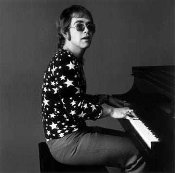 7th November 1970:  Portrait of British-born musician Elton John playing piano while wearing sunglasses and a shirt covered in stars.  (Photo by Jack Robinson/Hulton Archive/Getty Images)