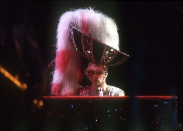 CIRCA 1974: Pop singer Elton John performs onstage at the piano wearing a giant fuzzy hat in circa 1974.  (Photo by Michael Ochs Archives/Getty Images)