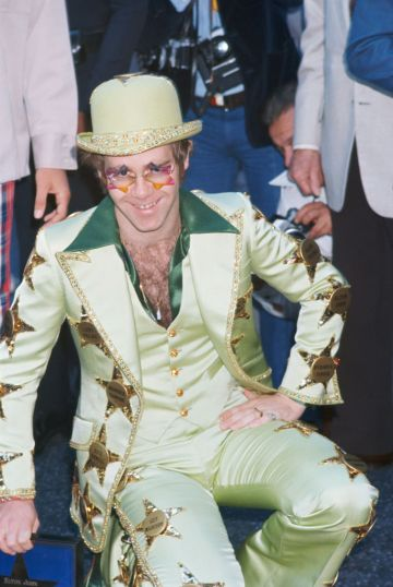 English singer-songwriter and pianist Elton John is honoured with a star on the Hollywood Walk of Fame, at 6915 Hollywood Boulevard, Los Angeles, 23rd October 1975. He is wearing a suit emblazoned with the names of stars, including his own. (Photo by Maureen Donaldson/Getty Images)