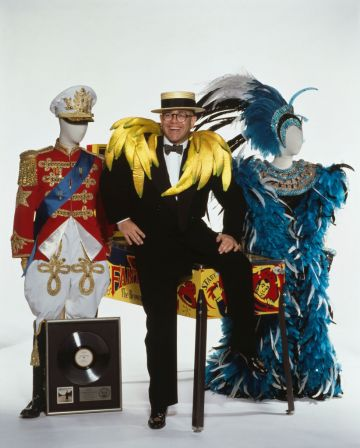 English pop singer Elton John with some of the items he will be putting up for auction at Sotheby's, London, 1988. Among the items are a platinum disc of his album 'A Single Man', a Captain Fantastic and the Brown Dirt Cowboy pinball machine by Bally, and a pair of outlandish stage costumes. John himself is wearing a set of satin bananas over his shoulders. (Photo by Georges De Keerle/Getty Images)