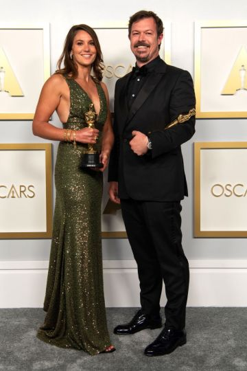 """Pippa Erlich and James Reed pose backstage with the Oscar for Documentary Feature for """"My Octopus Teacher"""" in the press room during the 93rd Annual Academy Awards at Union Station on April 25, 2021 in Los Angeles, California. (Photo by Matt Petit/A.M.P.A.S. via Getty Images)"""