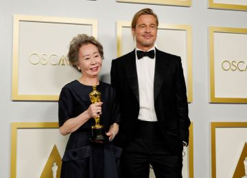 """Yuh-Jung Youn, winner of Best Actress in a Supporting Role for """"Minari,"""" poses with Brad Pitt in the press room at the Oscars on Sunday, April 25, 2021, at Union Station in Los Angeles. (Photo by Chris Pizzello-Pool/Getty Images)"""
