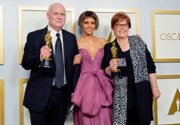 """Donald Graham Burt (L) and Jan Pascale (R), winners of Best Production Design for """"Mank"""", pose with Halle Berry (C) in the press room during the Oscars on Sunday, April 25, 2021, at Union Station in Los Angeles. (Photo by Chris Pizzello-Pool/Getty Images)"""