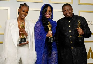 """Tiara Thomas, H.E.R., and Dernst Emile II, winners of Best Original Song for """"Fight For You"""" from """"Judas and the Black Messiah,"""" pose in the press room at the Oscars on Sunday, April 25, 2021, at Union Station in Los Angeles. (Photo by Chris Pizzello-Pool/Getty Images)"""