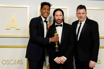"""Jon Batiste, Trent Reznor, and Atticus Ross, winners of Best Original Score for """"Soul,"""" pose in the press room during the Oscars on Sunday, April 25, 2021, at Union Station in Los Angeles. (Photo by Chris Pizzello-Pool/Getty Images)"""