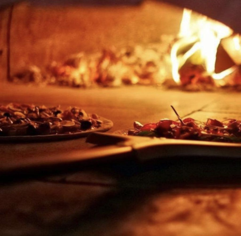 Pizzas cooking in wood-fired oven in Quattro