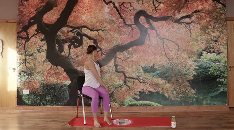 Pilates instructor turning around on a chair during chair yoga
