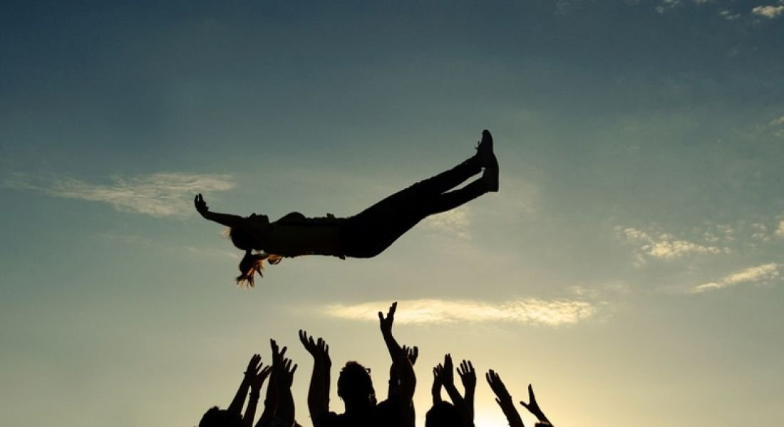 Tech industry: group of people throwing someone up in the air in celebration