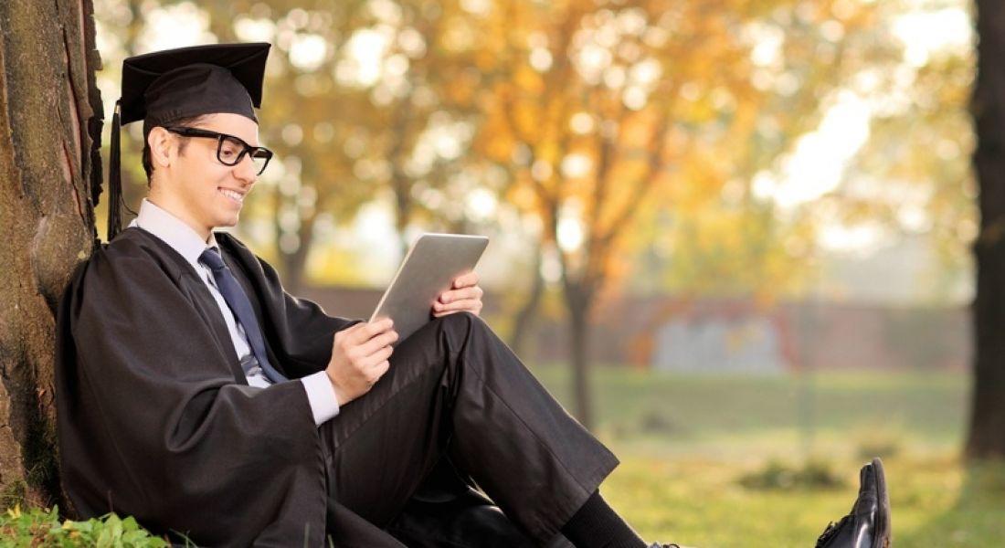 Graduate sitting under tree, using iPad