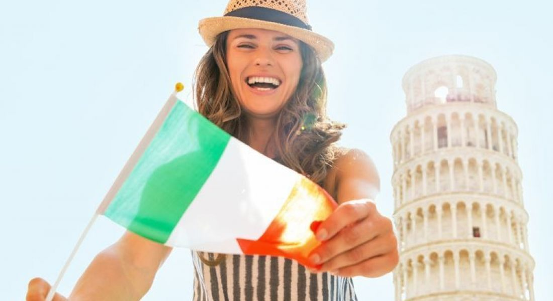 Italy: woman waving Irish flag in front of Leaning Tower of Piza