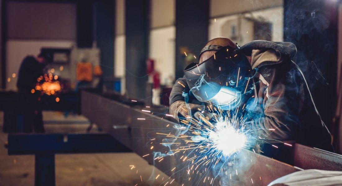 Industrial welder with torch and protective helmet in big hall.