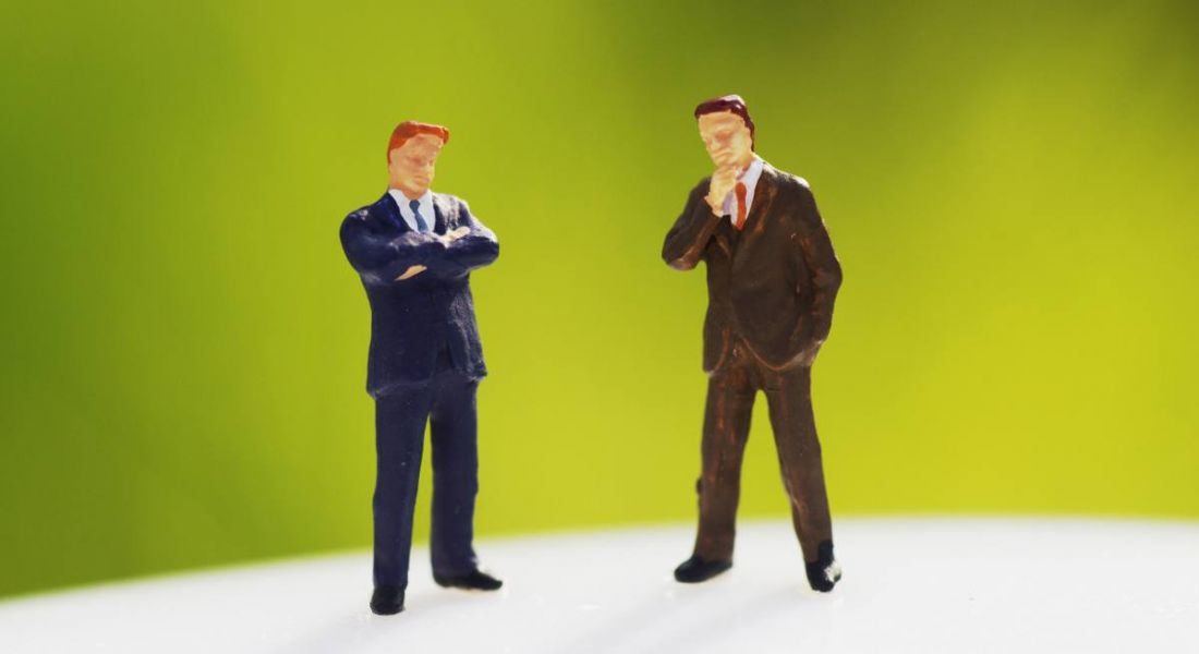 Two figurines in business suits with arms crossed looking confrontational against a lime green background.