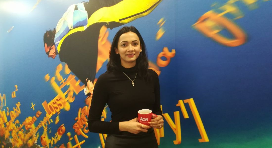 Young dark-haired woman in a dark polo neck standing in front of vivid mural holding a red coffee cup with Aon slogan.