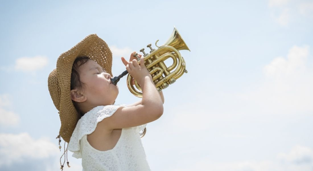 Girl playing trumpet triumphantly