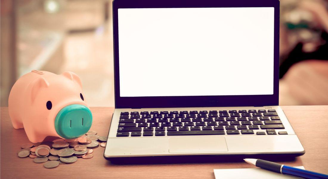Piggy bank beside a laptop fintech twitter