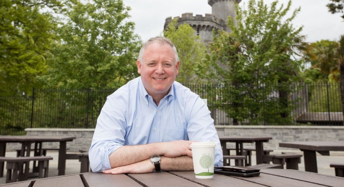 Niall O'Leary pictured having a coffee outside at a wooden table, a castle tower visible among the trees in the background
