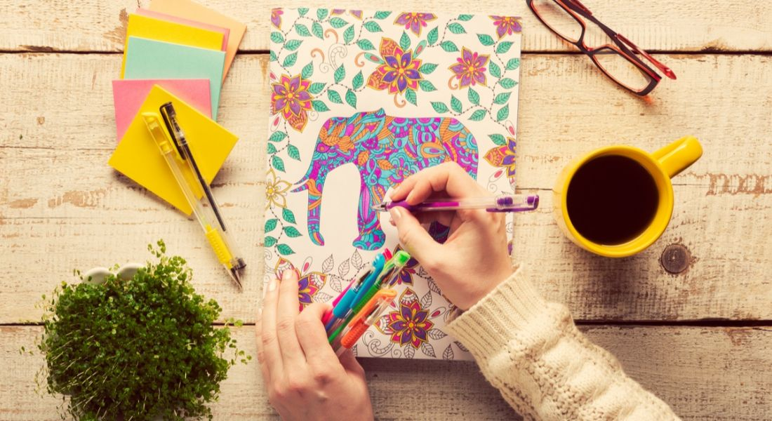Stress busters: A woman calmly colouring on a desk