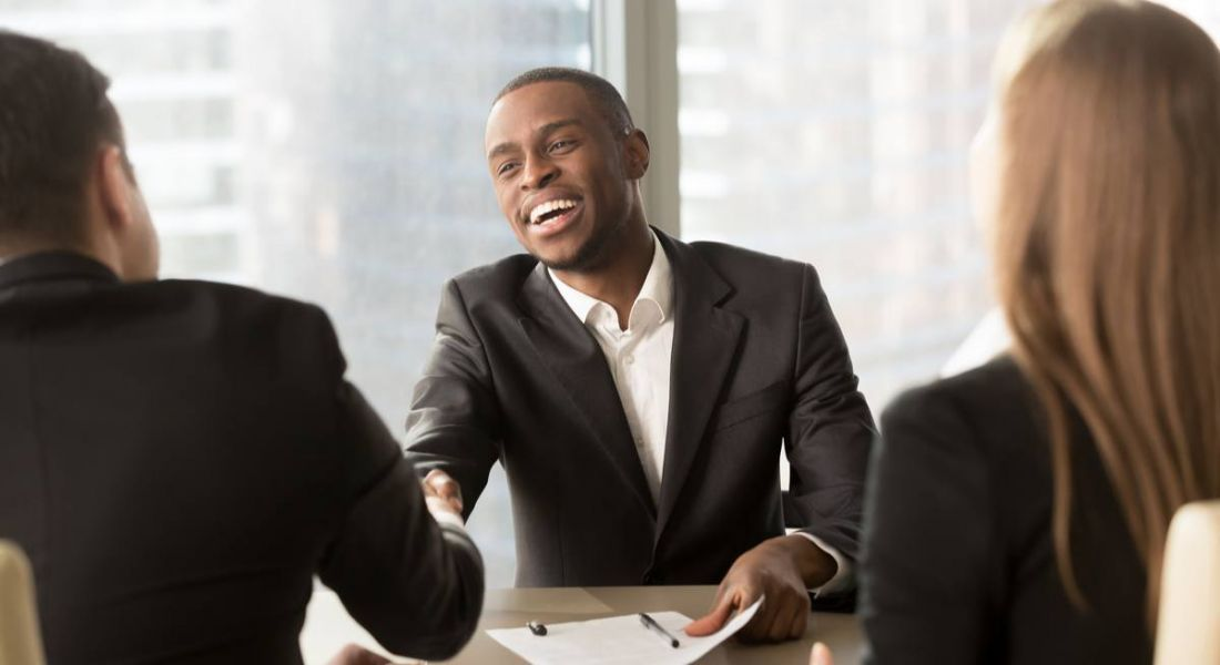 Excited businessman shaking hands with someone after being given a promotion.