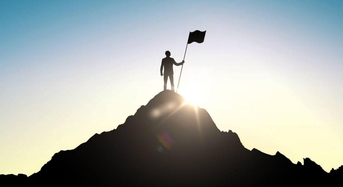 Person at the top of a mountain planting a flag. Depicts success despite having a bad leader.