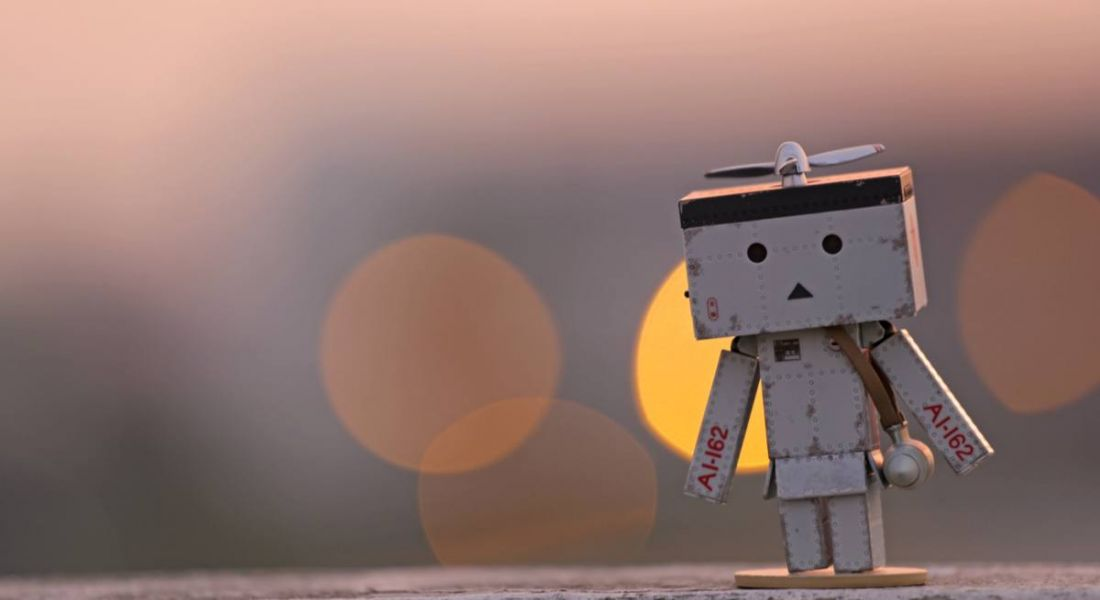 robot figure against the backdrop of a sunrise