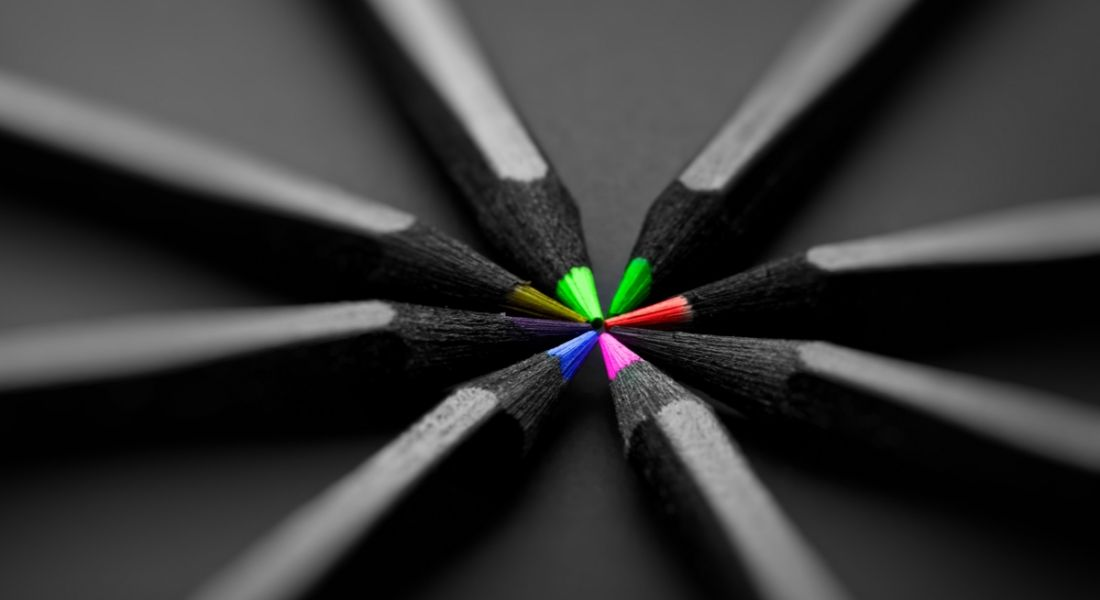 Black pencils on a black background with colourful tips depicting creativity