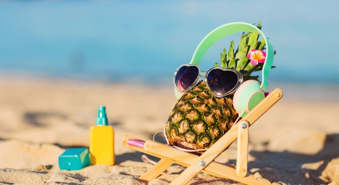 Pineapple on a small sunbed on the beach with sunglasses and headphones. Clearly listening to some top career podcasts.